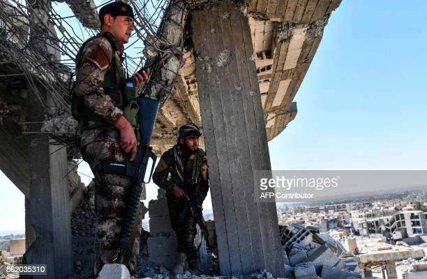 TOPSHOT Members of the Syrian Democratic Forces backed by US special forces walk on a building near Raqa's central hospital as they clear the last...