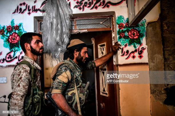 TOPSHOT Members of the Syrian Democratic Forces check a house as they advance to the next building on the eastern frontline in Raqa on September 25...
