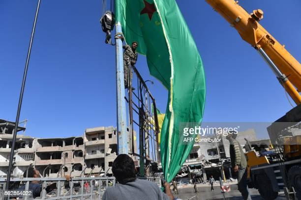 Members of the Syrian Democratic Forces put up their flag as preparations are ongoing for celebrations on the iconic AlNaim square in Raqa on October...
