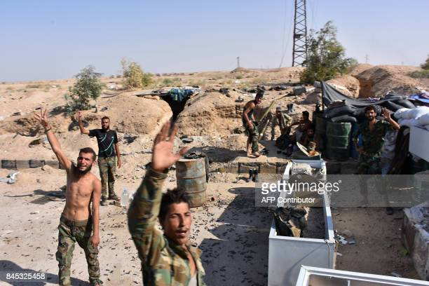 Members of the Syrian government forces flash the sign for victory at a checkpoint on the outskirts of Deir Ezzor on September 10 as they continue to...