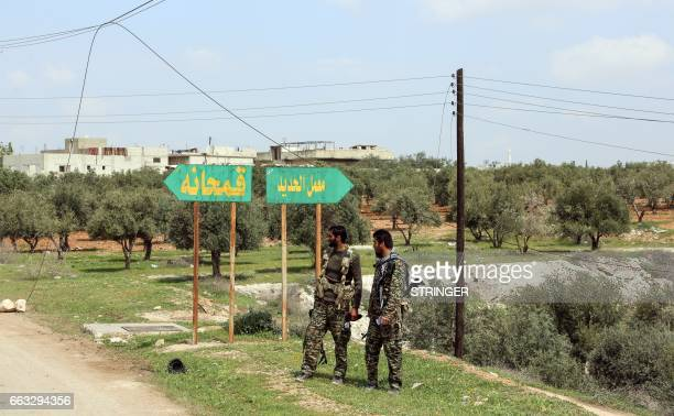 Members of the Syrian government forces stand at a crossroads near the town of Qumhanah in the countryside of the central province of Hama on April 1...