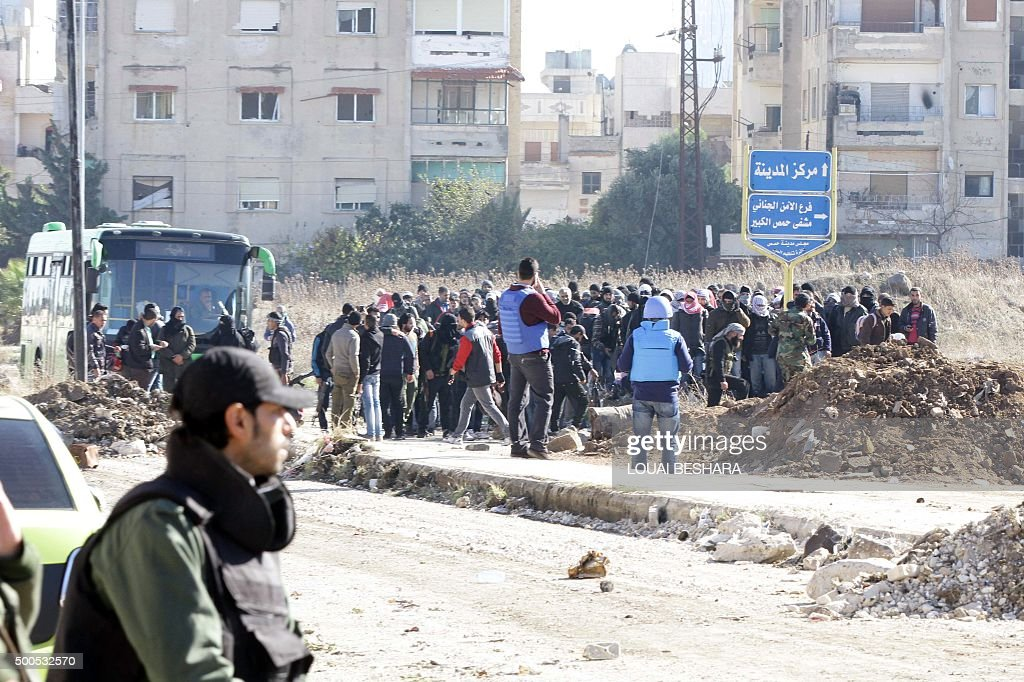 Members of the Syrian government forces stand guard as hundreds of civilians and Syrian rebel forces began evacuating the last oppositionheld...