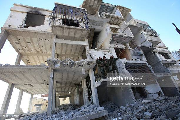 Members of the Syrian progovernment forces pose for a picture in a destroyed building in the strategic town of Salma in the coastal Latakia province...