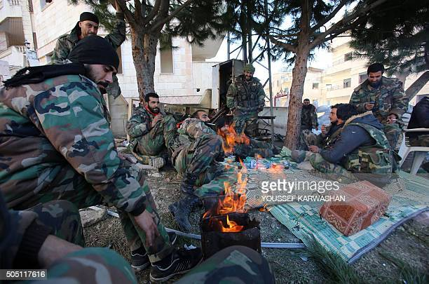Members of the Syrian progovernment forces rest in the strategic town of Salma in the coastal Latakia province on January 15 following its recapture...