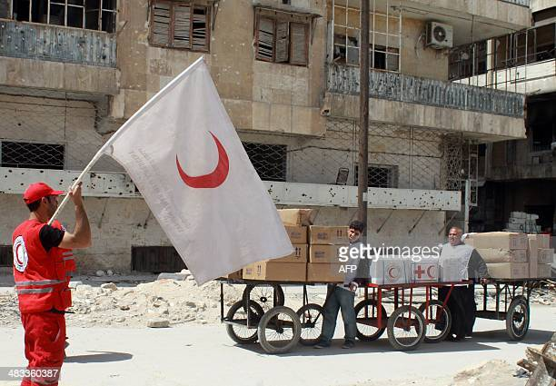 Members of the Syrian Red Crescent arrive with aid at the rebel controlled Garage alHajz checkpoint in the Bustan alQasr district of the northern...