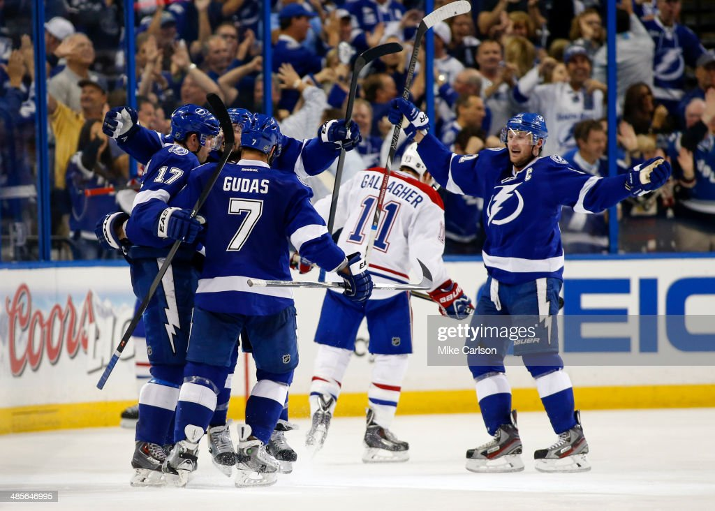 Members of the Tampa Bay Lightning, including (L-R) Alex Killorn #17, <a gi-track='captionPersonalityLinkClicked' href=/galleries/search?phrase=Radko+Gudas&family=editorial&specificpeople=5648763 ng-click='$event.stopPropagation()'>Radko Gudas</a> #7 and <a gi-track='captionPersonalityLinkClicked' href=/galleries/search?phrase=Steven+Stamkos&family=editorial&specificpeople=4047623 ng-click='$event.stopPropagation()'>Steven Stamkos</a> #91 celebrate a goal as <a gi-track='captionPersonalityLinkClicked' href=/galleries/search?phrase=Brendan+Gallagher&family=editorial&specificpeople=3704208 ng-click='$event.stopPropagation()'>Brendan Gallagher</a> #11 of the Montreal Canadiens reacts in Game One of the First Round of the 2014 Stanley Cup Playoffs at the Tampa Bay Times Forum on April 16, 2014 in Tampa, Florida.