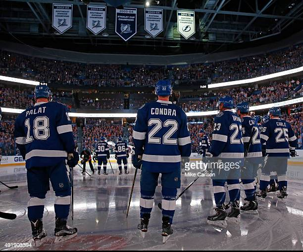 Members of the Tampa Bay Lightning watch as the Eastern Conference Championship banner is revealed prior to the seasonopening game against the...