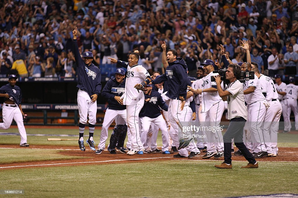 Members of the Tampa Bay Rays wait for Jose Lobaton #59 of the Tampa Bay Rays at home plate after he hit a walk off a game home run to defeat the Boston Red Sox in Game 3 of the American League Division Series on Monday, October 7, 2013 at Tropicana Field in St. Petersburg, FL.