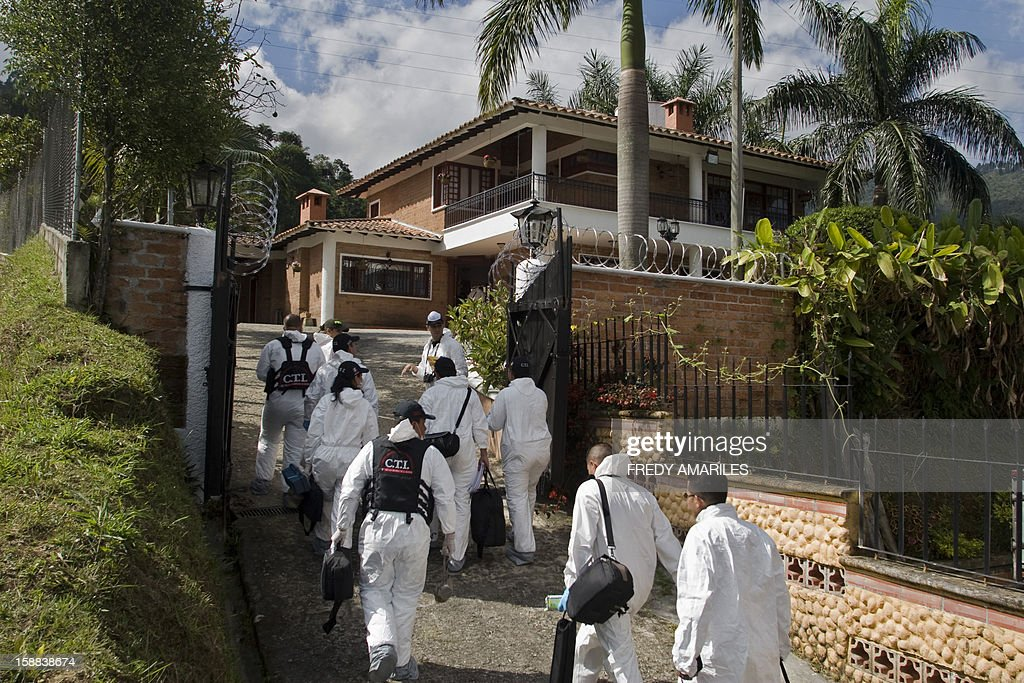 Members of the Technical Investigation Unit of the Prosecutor (CTI) arrive at a villa located in the rural municipality of Envigado, near Medellin, capital of Antioquia department, 400 km northwest of Bogota, to remove the bodies of nine people who were shot and killed apparently during a party, on December 31, 2012. None of the four women and five men who were slain have been identified, no suspects have been arrested and authorities have no idea what the motive of the killings might be, said Yesid Vasquez, police chief for Antioquia. AFP PHOTO/Fredy AMARILES