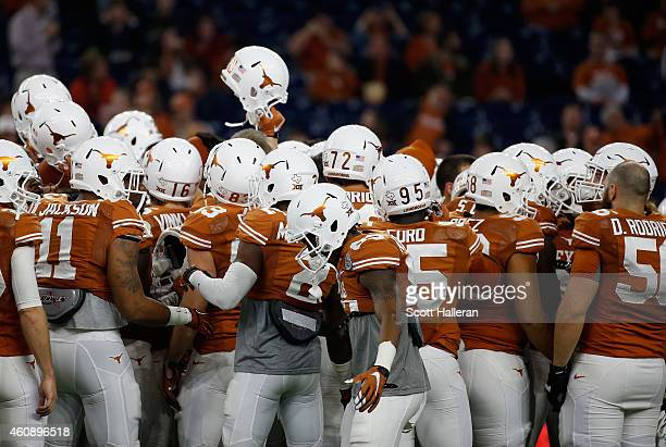 Members of the Texas Longhorns huddle on the field before the start of their game against the Arkansas Razorbacks at the AdvoCare V100 Texas Bowl at...