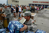 Members of the Texas National Guard distribute ice and water to residents affected by Hurricane Ike September 14 2008 in Galveston Texas Ike made...