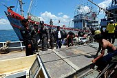 Members of the Thai Royal Marine Police stand on the deck of a seized fishing boat after the police intercepted three fishing vessels and detained 23...