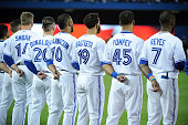 Members of the Toronto Blue Jays are seen on the base path during the signing of the Canadian and American national anthems before the home opener...