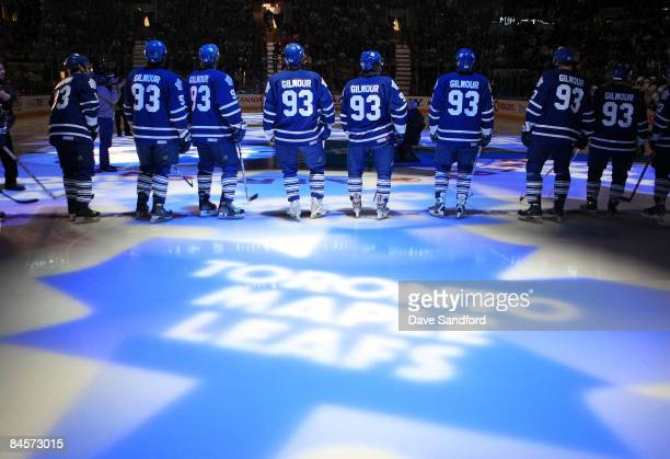 Members of the Toronto Maple Leafs stand on the blue line wearing the to honor Doug Gilmour as he has his jersey raised to the rafters prior to...