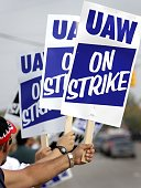 Members of the United Auto Workers hold up signs and strike in front of the General Motors Flint Truck Assembly Plant September 25 2007 in Flint...