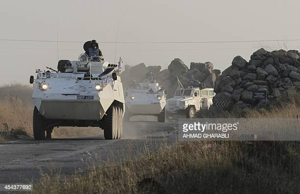 Members of the United Nations Disengagement Observer Force drive their armoured vehicles in the Israeliannexed Golan Heights near the Quneitra...
