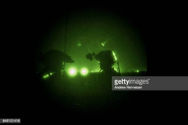Members of the United States Army Special Forces Operational Detachment Alpha through a night vision goggle during casevac night training of...