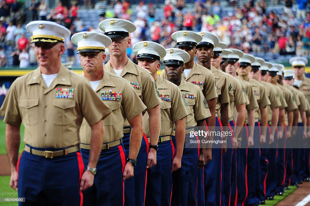 Members of the United States Marine Corps stand at attention down the first base line before the game between the Atlanta Braves and the Philadelphia...
