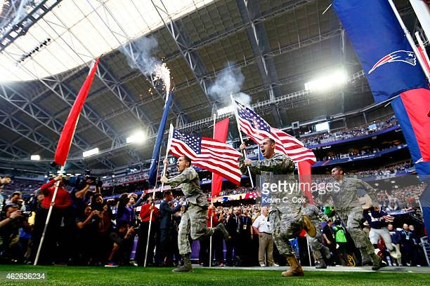 Members of the United States military run onto the field prior to Super Bowl XLIX between the Seattle Seahawks and the New England Patriots at...
