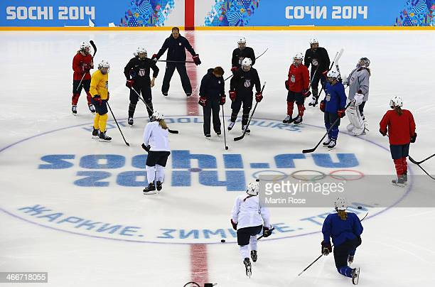 Members of the United States women's ice hockey team warm up during a training session ahead of the Sochi 2014 Winter Olympics at Shayba Arena on...