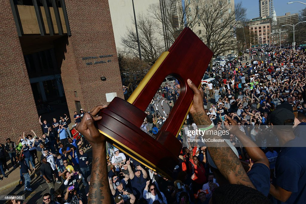 Members of the University of Connecticut's mens basketball team hold up the NCAA championship trophy during a victory parade to celebrate their national championship April 13, 2014 in Hartford, Connecticut. This year was the second time both the men's and women's Uconn basketball teams have won national championships in the same year.