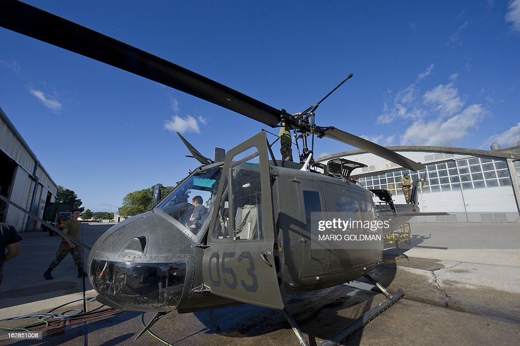 Members of the Uruguayan Air Force Brigade 1 repair a helicopter at the Air Base in Canelones, near Montevideo, on February 27, 2013. AFP PHOTO/Mario Goldman
