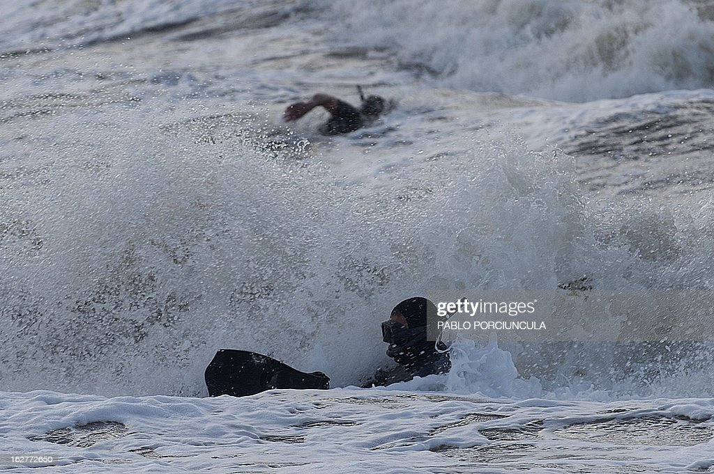 Members of the Uruguayan Air Force Operations, Training and Rescue Unit, swim before a drill in Montevideo, Uruguay on February 26, 2013.AFP PHOTO/Pablo PORCIUNCULA