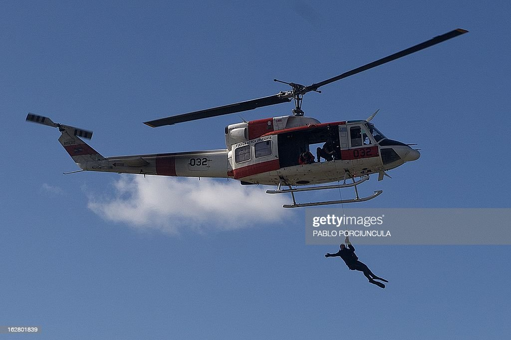 Members of the Uruguayan Air Force Operations, Training and Rescue Unit, take part in a drill at a beach of Salinas, near Montevideo, Uruguay on February 27, 2013. AFP PHOTO/Pablo PORCIUNCULA