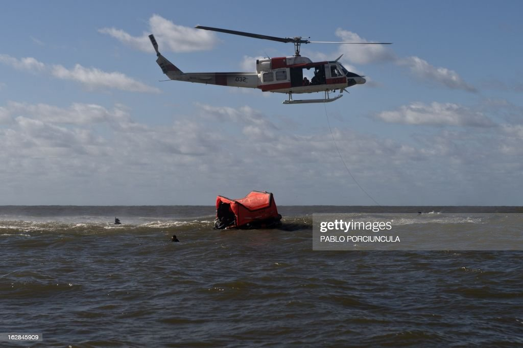 Members of the Uruguayan Air Force Operations, Training and Rescue Unit take part in a drill at a beach of Salinas, near Montevideo, Uruguay, on February 27, 2013. AFP PHOTO/Pablo PORCIUNCULA