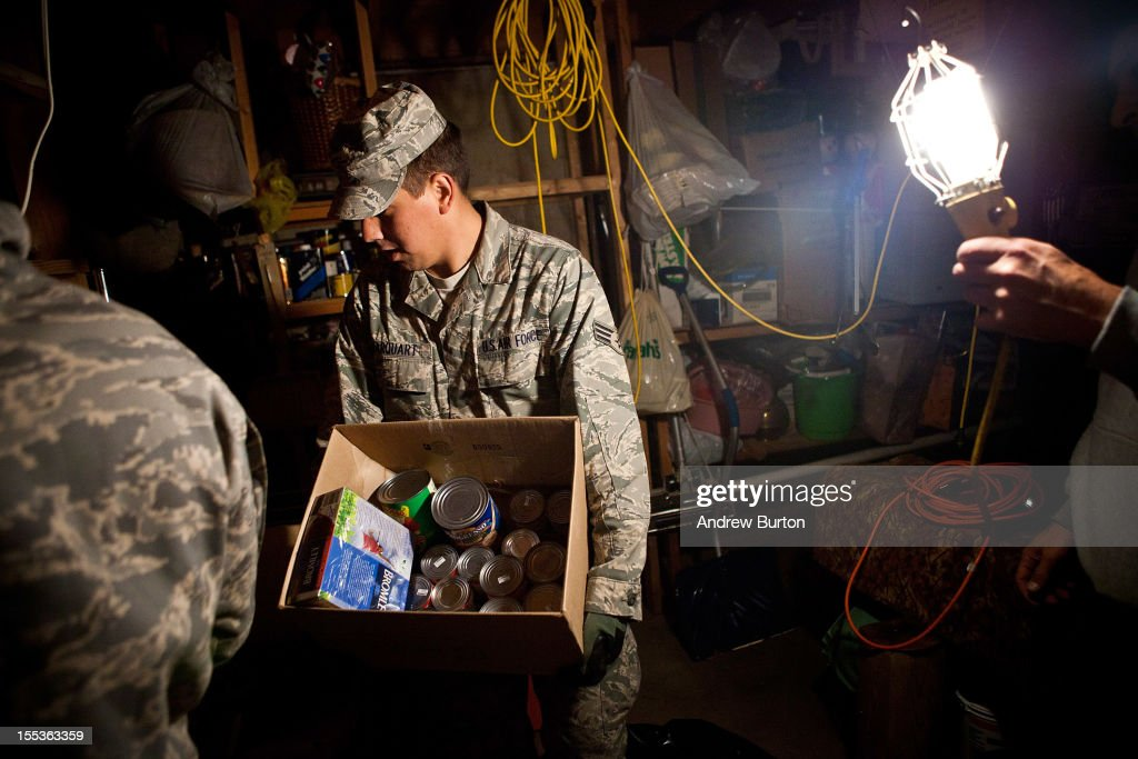 Members of the US Air Force National Guard collect canned goods donated by a man living in the Midland Beach neighborhood of Staten Island on November 3, 2012 in New York City. As clean up efforts from Superstorm Sandy continue, colder weather and another storm predicted for next week are beginning to make some worried.