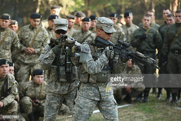 Members of the US Army 173rd Airborne Brigade demonstrate urban warfare techniques as Ukrainian soldiers look on on the second day of the 'Rapid...