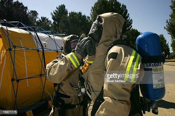 Members of the US Army 9th Civil Support Team make last minute adjustments to their suits before entering a hazardous crash zone during an exercise...