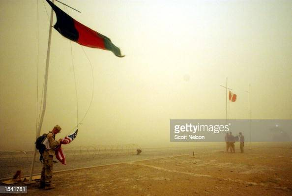 Members of the US Army Alpha Company 2nd Batallion 187 regiment flag detail hastily lower American flags during a sudden dust storm May 13 2002 at...