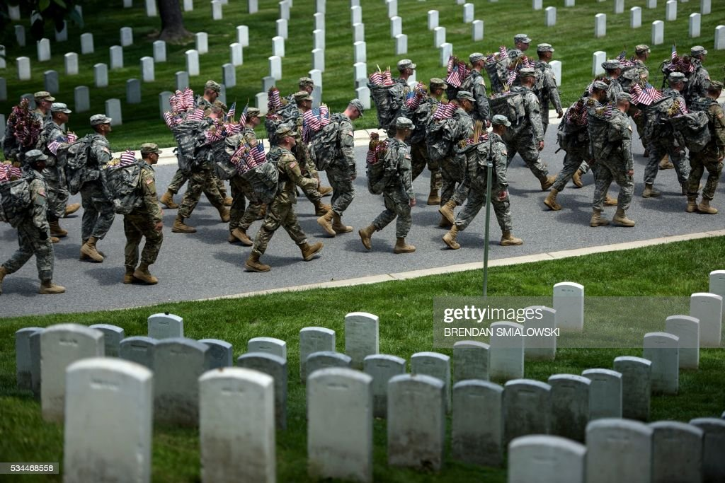 Members of the US Army march with miniature American flags to place at graves in Arlington National Cemetery on May 26, 2016 in preparation for Memorial Day in Arlington, Virginia. / AFP / Brendan Smialowski