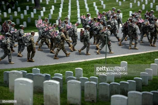 Members of the US Army march with miniature American flags to place at graves in Arlington National Cemetery on May 26 2016 in preparation for...