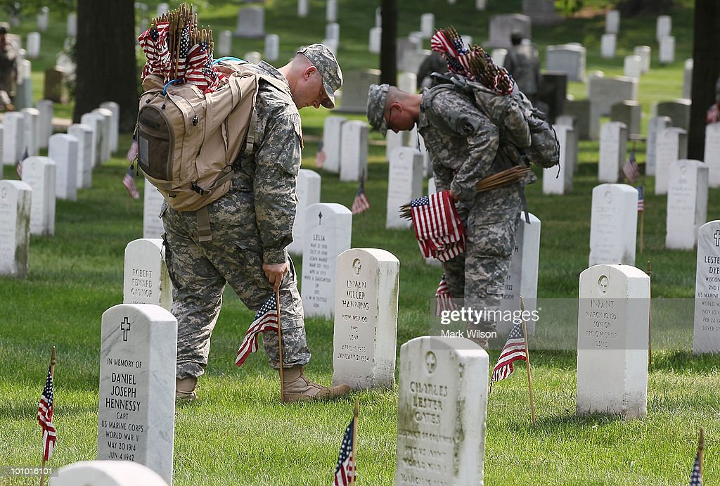 Members of the U.S. Army Old Guard place flags at gravesites at Arlington National Cemetery May 27, 2010 in Arlington, Virginia. About 1,300 soldiers, sailors and Marines in about three hours placed a flag at each of the more than 300,000 gravestones at Arlington ahead of the Memorial Day weekend.