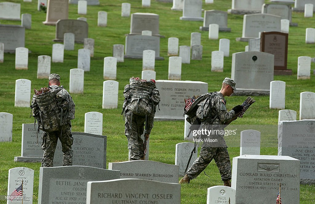 Members of the U.S. Army Old Guard place flags at gravesites at Arlington National Cemetery May 27, 2010 in Arlington, Virginia. It took 1,300 soldiers, sailors and Marines about three hours to place a flag at each of the more than 300,000 gravestones at Arlington ahead of the Memorial Day weekend.