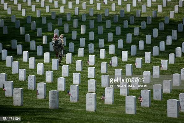 TOPSHOT Members of the US Army place American flags at graves at Arlington National Cemetery May 26 2016 in Arlington Virginia in preparation for...