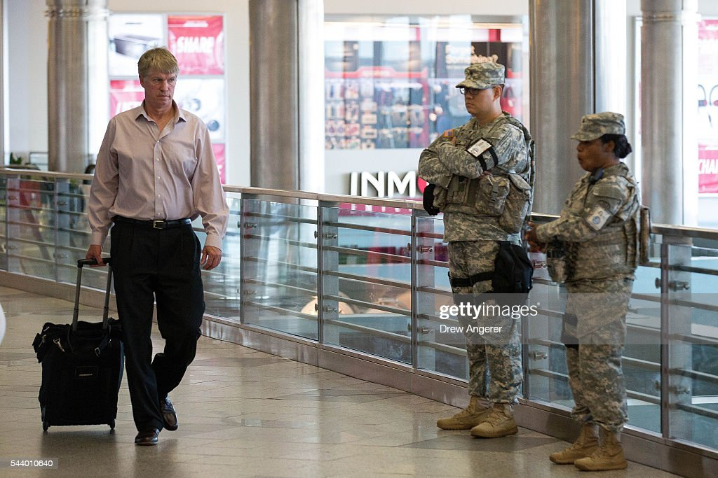 Members of the U.S. Army (R) stand guard as people walk through a concourse in the departures area at LaGuardia Airport (LGA), June 30, 2016 in the Queens borough of New York City. Following Tuesday's terrorist attacks at Instanbul's Ataturk Airport, the Transportation Security Administration and other law enforcement agencies have increased security at major airports in the United States.