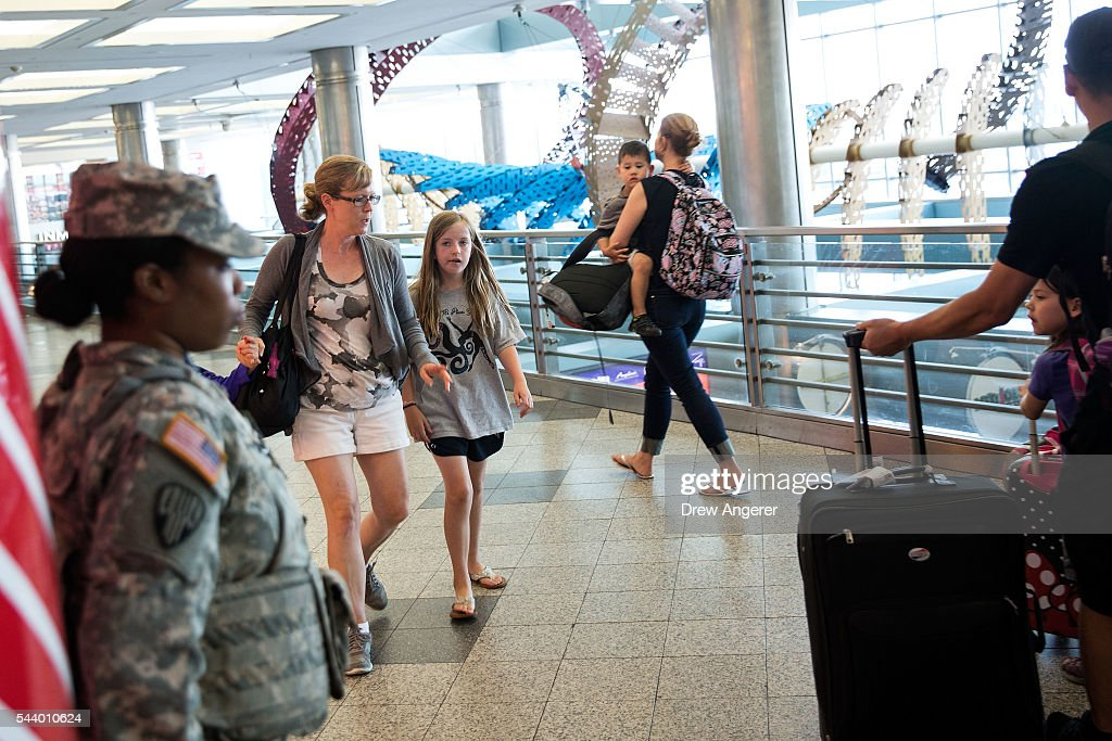 Members of the U.S. Army (L) stands guard as people walk through a concourse in the departures area at LaGuardia Airport (LGA), June 30, 2016 in the Queens borough of New York City. Following Tuesday's terrorist attacks at Instanbul's Ataturk Airport, the Transportation Security Administration and other law enforcement agencies have increased security at major airports in the United States.