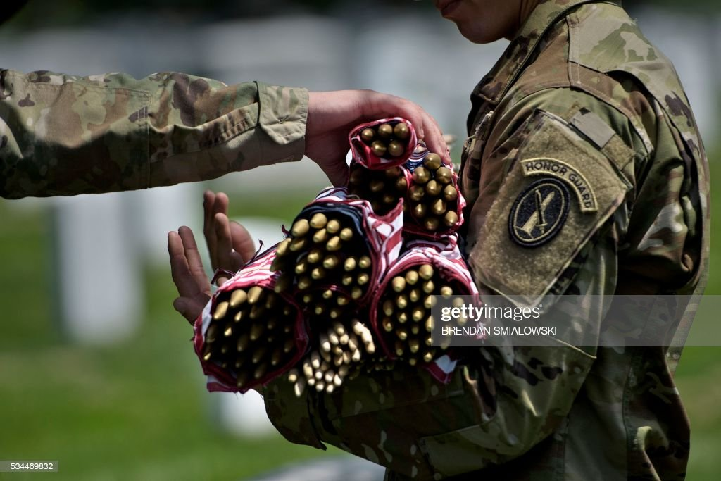 Members of the US Army stock up on American flags before placing them at graves in Arlington National Cemetery on May 26, 2016 in Arlington, Virginia in preparation for Memorial Day. / AFP / Brendan Smialowski