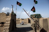 Members of the US Army wait at a police station while meeting with Afghan police officers near Kandahar Airfield on June 3 2014 Members of the 1st...