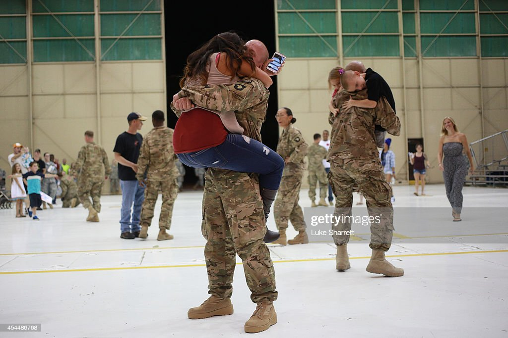 Members of the US Army's 159th Combat Aviation Brigade 101st Airborne Division embrace family members following a homecoming ceremony at Campbell...