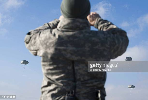 Members of the US Army's 4th Infantry Brigade Combat Team 25th Infantry Division part of the NATOled peacekeeping mission in Kosovo parachute as they...