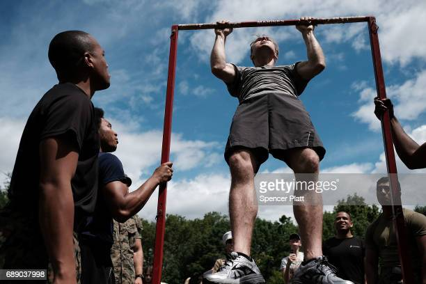 Members of the US Marine Corps watch as Matt Cortright does pullups in Brooklyn's Prospect Park as part of Fleet Week on May 27 2017 in New York City...