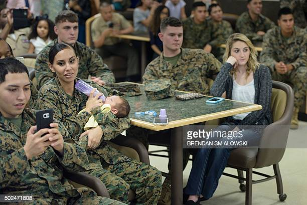 Members of the US Marines their loved ones and others listen while US President Barack Obama speaks to celebrate the holidays during Christmas Day at...