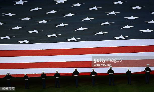 Members of the US military hold a giants flag on the field as the National Anthem is performed prior to the start of the opening day game between the...
