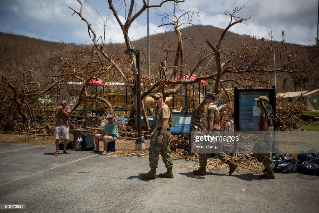 Members of the U.S. military pass people waiting for transportation after Hurricane Irma in St John, U.S. Virgin Islands, on Tuesday, Sept. 12, 2017. After being struck by Irma last week, the U.S. Virgin Islands couldnt look less like a tourist destination. Many local residents are giving up and getting out after losing everything to the category 5 storm,even as the local authorities in the U.S. territory say they are determined to rebuild the islands. Photographer: Michael Nagle/Bloomberg via Getty Images