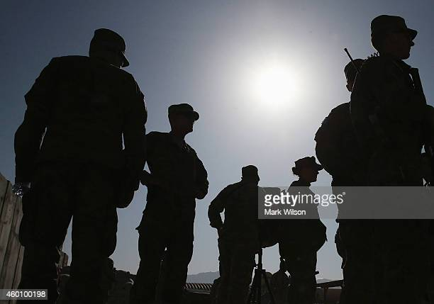 Members of the US military stand by after listening to US Secretary of Defense Chuck Hagel speak to American troops December 7 2014 in FOB Gamberi...