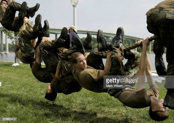 Members of the US Naval Academy Freshman class try to hang from a rope for one minute without touching the ground during an event called 'Sea Trials'...